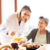 portrait of caregiver preparing food for senior woman