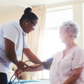 portrait of caregiver checking blood pressure of senior woman